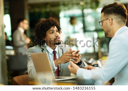 Men are sitting at table in modern cafe. Talk about work #1483236155