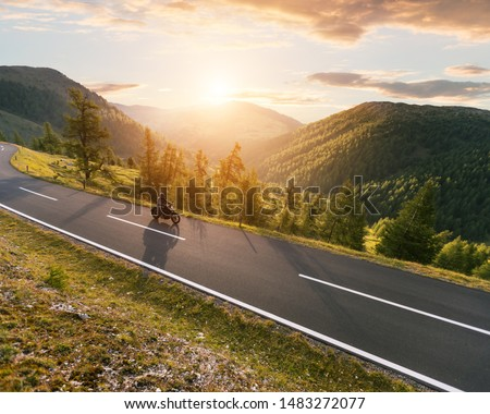 Motorcycle driver riding in Alpine landscape. Lifestyle photo in sunset. #1483272077