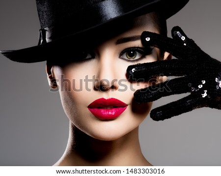 Сlose-up portrait of a woman in a black hat and gloves with red lips posing at studio #1483303016