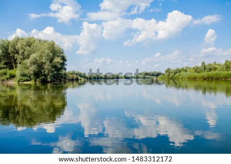 Blue beautiful sky against the background of the river. Clouds are displayed in calm water. On the horizon, the green bank of the Dniester, place for fishing. #1483312172