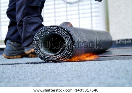 Flat roof installation with propane blowtorch during construction works with roofing felt. Heating and melting bitumen roofing felt. Roofing felt. Roofer working. Roofer working tool. Waterproofing #1483317548
