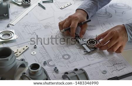 Engineer technician designing drawings mechanicalparts engineering Enginemanufacturing factory Industry Industrial work project blueprints measuring bearings caliper tools #1483346990