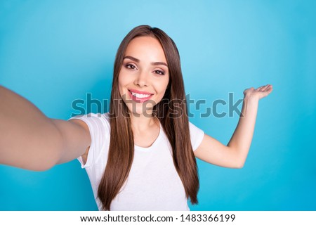 Close up photo of cheerful lovely youth making photo smiling at camera vlog wearing white t-shit isolated over blue background #1483366199