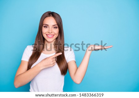 Portrait of lovely millennial holding hand pointing to ads with her index finger isolated over blue background #1483366319