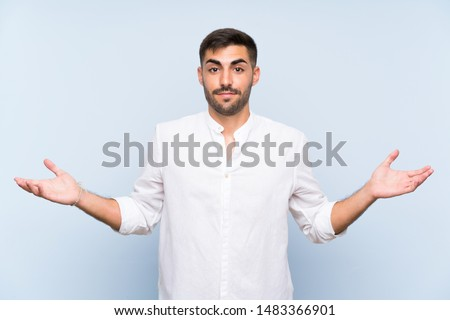 Handsome man with beard over isolated blue background having doubts while raising hands #1483366901