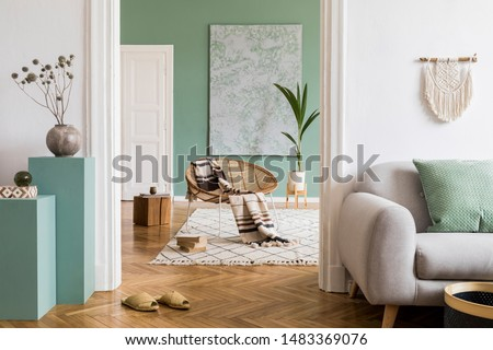 Modern and bohemian composition of interior design at apartment with gray sofa, rattan armchair, wooden cubes, plaid, tropical plant, macrame and elegant accessories. Stylish home decor. Template. #1483369076
