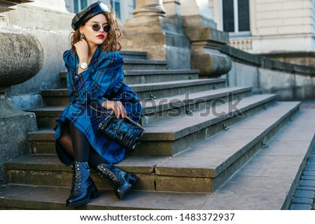 Outdoor full-length portrait of pretty curly lady wearing trendy autumn checkered dress, leather beret, glasses, wrist watch, black tights, boots, holding small bag, posing in street. Copy space #1483372937