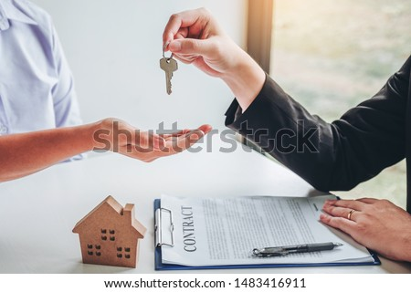 Sale Agent giving house keys to woman customer and sign agreement documents for realty purchase. #1483416911
