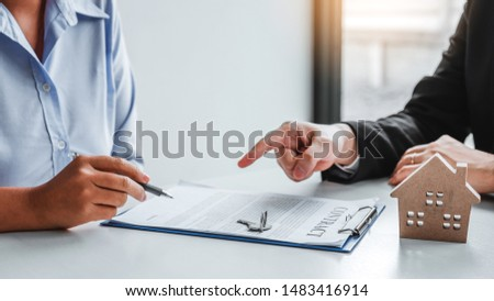 Sale Agent giving house keys to woman customer and sign agreement documents for realty purchase. #1483416914