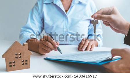 Sale Agent giving house keys to woman customer and sign agreement documents for realty purchase. #1483416917