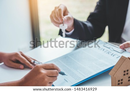 Sale Agent giving house keys to woman customer and sign agreement documents for realty purchase. #1483416929