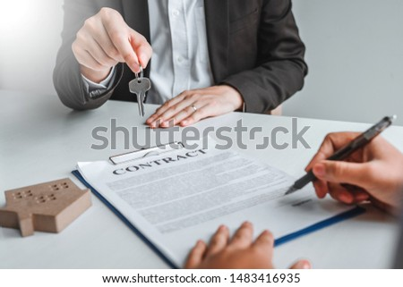 Sale Agent giving house keys to woman customer and sign agreement documents for realty purchase. #1483416935
