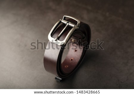 Fashionable men's brown belt made of genuine leather with a light metal buckle on a dark background. Genuine leather, handmade Royalty-Free Stock Photo #1483428665