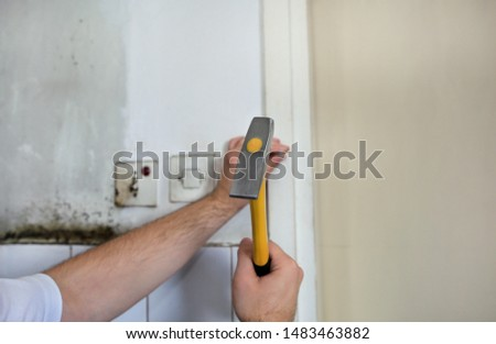 Construction worker and handyman working on renovation work. Builder with yellow hammer strikes and nails a nail into wooden wall of kitchen door at construction site. Apartment renovation concept. #1483463882