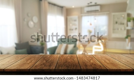 Wood table in modern home room interior with empty copy space on the table for product display mockup. Furniture design and home decoration concept. #1483474817