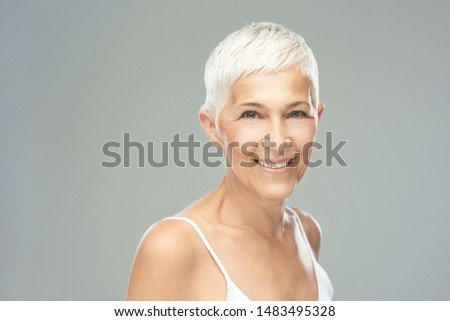 Beautiful smiling senior woman with short gray hair posing in front of gray background. Beauty photography. #1483495328