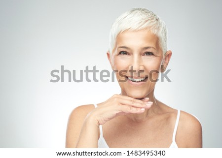 Beautiful smiling senior woman with short gray hair posing in front of gray background. Beauty photography. #1483495340