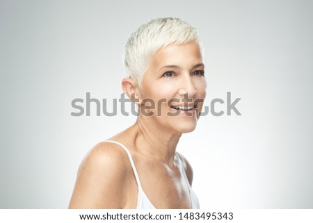 Beautiful smiling senior woman with short gray hair posing in front of gray background. Beauty photography. #1483495343