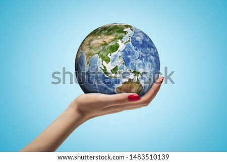 Side closeup of woman's hand facing up and holding small Earth on light blue background. Choose planet's future. Care about nature. Promote sustainability. #1483510139