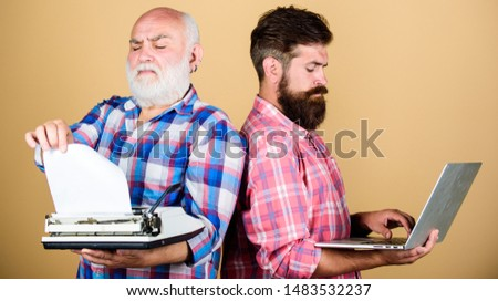 father and son. technology development and improvement. technology generation battle. Modern life. retro typewriter vs laptop. youth vs old age. business approach. two bearded men. Vintage typewriter. #1483532237