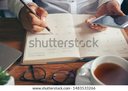 Planner plan Schedule Calendar and reminder agenda, work online at home. Women'hand planning daily appointment and note holiday trip in diary at office desk. Calendar reminder event concept. #1483533266