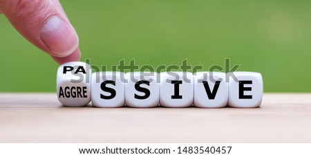 "Hand turns a dice and changes the word ""passive"" to ""aggressive"", or vice versa. Royalty-Free Stock Photo #1483540457"