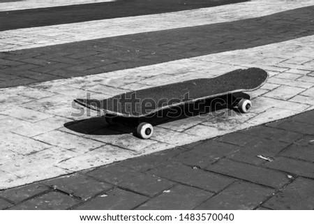 Skateboad on the floor. Dark black and white photo. #1483570040