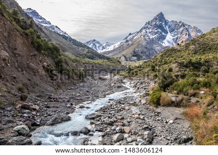Andes valleys inside central Chile at Cajon del Maipo, an amazing rugged landscape with steep mountains and an awe scenery with the river in the valley surrounded by forest and snowcapped mountains Royalty-Free Stock Photo #1483606124