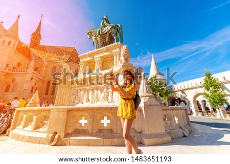 A young woman taking pictures of a landmark in the castle of Budapest in Hungary.