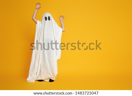 Happy Halloween! Cute little kid in ghost costume on yellow background. Royalty-Free Stock Photo #1483725047