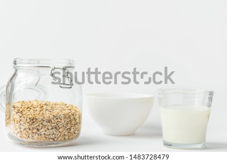 Glass of non-dairy animal-free plant based milk rolled oats in reusable crystal jar bowl on white kitchen table. Healthy breakfast energy fitness concept #1483728479