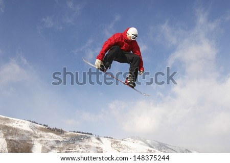 Low angle view of young male snowboarder jumping against cloudy sky #148375244