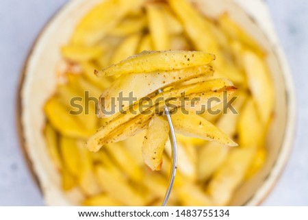 French fries. Homemade, roasted french-fried potatoes. Top above view on table. Junk food. Pricked on fork #1483755134
