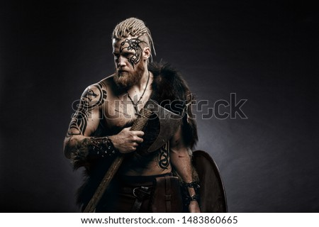 Medieval warrior berserk Viking with tattoo on skin, red beard and braids in hair with axe and shield attacks enemy. Concept historical photo #1483860665