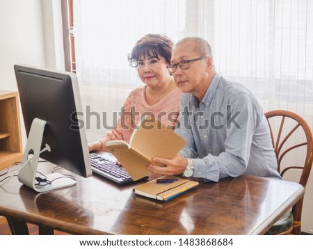elder couple using computer together with book at home #1483868684