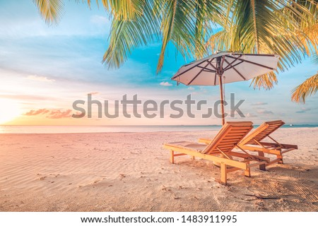 Beautiful tropical sunset scenery, two sun beds, loungers, umbrella under palm tree. White sand, sea view with horizon, colorful twilight sky, calmness and relaxation. Inspirational beach resort hotel #1483911995