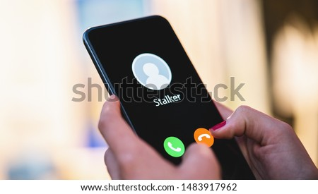 Phone call from a anonymous stalker. Stalking or bullying with phone concept. Stalker caller, scammer or stranger. Woman answering a incoming call. Ex boyfriend with fake identity. #1483917962