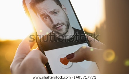 Dating app in mobile phone screen. Woman swiping and liking profiles on relationship site or application. Single woman using smartphone to find love, partner and boyfriend. Mockup website. #1483917971