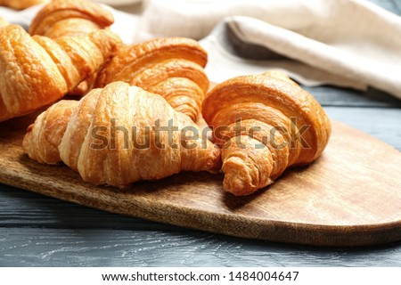 Board with tasty croissants on dark wooden table, closeup. French pastry #1484004647