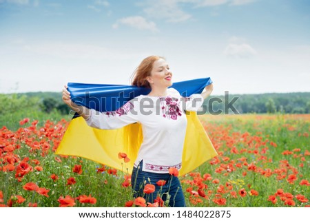 Girl carries fluttering blue and yellow flag of Ukraine in field. Ukraine's Independence Flag Day. Constitution day. Woman in traditional embroidery with flag of Ukraine. 24 August. Patriotic holiday. #1484022875