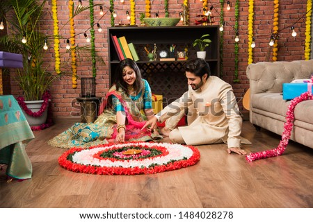 Indian couple making flower Rangoli on Diwali or Onam Festival, taking selfie or holding sweets #1484028278