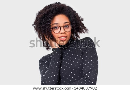 Pretty dreamy dark-skinned young woman dressed in black with white dots blouse, holding hands on head, feel happy. African American female smiling broadly, wearing round eyewear posing over white wall #1484037902
