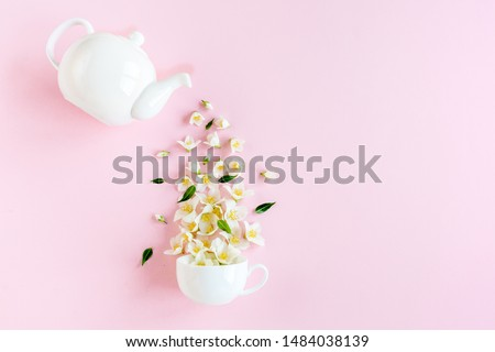 Creative layout of teapot and tea Cup with Jasmine flowers on a pink background. Jasmine tea. #1484038139
