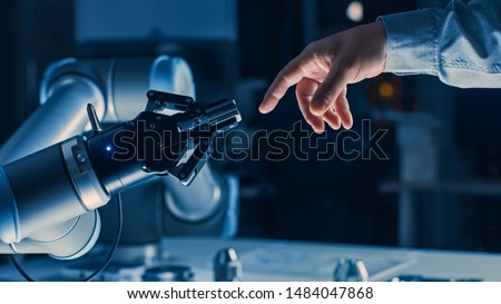 Futuristic Robot Arm Touches Human Hand in Humanity and Artificial Intelligence Unifying Gesture. Conscious Technology Meets Humanity. Concept Inspired by Michelangelo's Creation of Adam Royalty-Free Stock Photo #1484047868