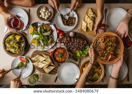 large and generously covered with delicious dishes table, covered with a tablecloth on which there are various delicious dishes of Ukrainian cuisine: fried ribs, borsch, salads, cheese #1484080679