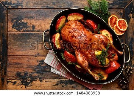 Roast goose stuffed with baked apples in a skillet on a dark wooden background, festive christmas recipe. Top view with copy space.