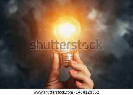 Idea and Innovation concept. Lamp or Light Bulb in Female Hand as Symbol of Inspiration on dark background #1484128352