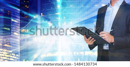 Respectable young businessman signing documents on background with blurred skyscraper #1484130734
