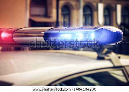 Red and blue signal lights on the roof of a traffic police patrol car