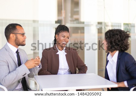 Happy business colleagues meeting in hallway or canteen. Multiethnic business team sitting at table, talking, chatting, laughing. Corporate communication concept #1484205092